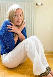 eine junge frau sitzt vor einem heizkörper im winter raumtemperatur ist zu niedrig