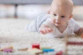 niedliches baby erreicht für holzspielzeug auf wohnzimmer teppich stockfoto und mehr bilder 6 11 monate