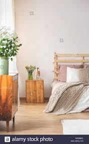 gemütliches schlafzimmer mit holzmöbeln und blumen