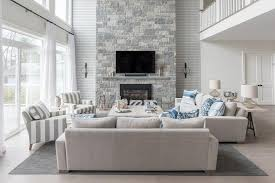blue and gray living room with a two story fireplace