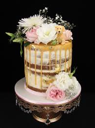 Double barrel caramel mudcake with white chocolate buttercream and a caramel drip Decorated with fresh