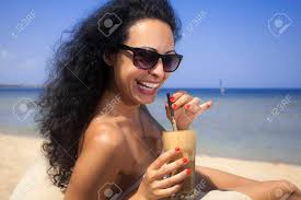 Young Beautiful Brunette Girl Drinking Iced Coffee On The Beach