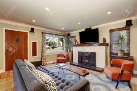 offenes konzept wohnzimmer in der amerikanischen handwerker stil haus mit beigefarbenen wänden holzböden einem standard kamin und eine wand tv