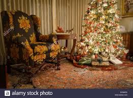 Indoor Christmas Tree With Presents Underneath Next To Chair