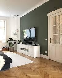 grüne wand im wohnzimmer stimmig mit braunem fußboden und