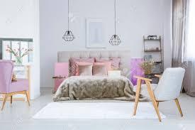 poster an weißer wand über grauem bett mit rosa accessoires und felldecke im geräumigen schlafzimmer