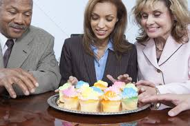 Businesspeople Eating Cupcakes In Office Stock Photo