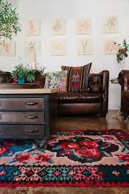 Comfy Living Room With Leather Couches Kilim Cushions And Huge Bright Jewel Tone Floral Rug