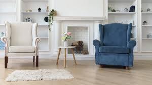 weißer und blauer sessel mit weißem modernem tisch vor kamin