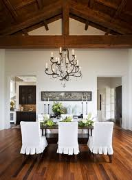Beautiful Dining Room Design With Cathedral Ceiling Iron Crystal Chandelier Wood Rectangular Table White Ruffled Slip Covered Chairs