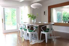 A Unique Pairing Of White Chairs With Forest Green Cushions Fits Nicely This Deep Brown Wooden Table And The Animal Hide Rug Is Nice Touch