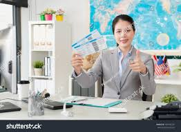 Professional Young Female Travel Agent Office Worker Holding Airline Tickets Face To Camera And Showing Thumb