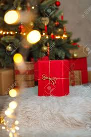 A Big Red Gift Stands Under The Christmas Tree Background For Holiday