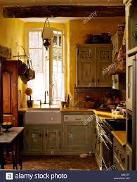 Pale Gray Green Distressed Cupboards In Yellow French Country Kitchen With Terracotta Tiled Floor And Belfast Sink