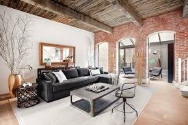 Living Room With Exposed Brick Wood Beams And Gray Sectional