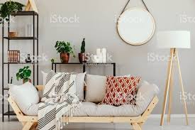 weiße holz le neben stilvollen skandinavischen mit gemusterten kissen und decke im eleganten wohnzimmer interieur mit beige wand stockfoto