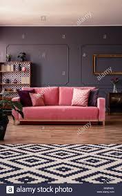 pink velvet sofa mit kissen in der mitte des dunklen grau