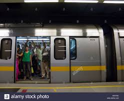 A yellow line tube train carriage with open doors at a platform at