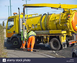 Two Council Workmen Using A Sewer Cleaning Truck To Flush And Clean ...