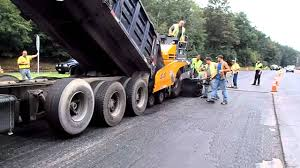 100 Dump Truck Drivers Truck Feeding Asphalt Into The Paver As The Paver Pushes The