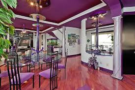 Dining Room With Purple Accent Wall Wood Flooring And Light Table Set