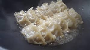Close Up Cooking Fried Dumplings In A Frying Pan Chinese Food With Hot Steams