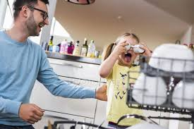 Playful Daughter And Father Clearing Dishwasher Stock Photo