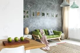 holztisch mit drei grünen äpfeln im wohnzimmer mit roher wand