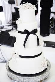 Five Tiered Wedding Cake With White Flowers And Black Ribbon