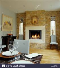 Lighted Fire Fireplace Exposed Brick Wall Modern Dining Room With White Leather Chairs And Wooden Flooring