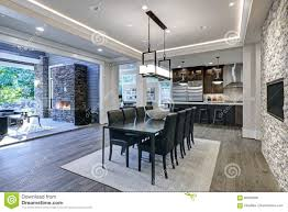 Modern Open Floor Plan Dining Room Design Accented With Stone Fireplace Wall Facing Black Table Leather Chairs Overlooking Lush Outdoors