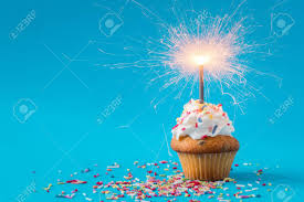 Birthday Cupcake with a sparkler on blue background Stock