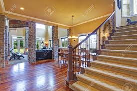 luxus haus mit hohen decken steinsäulen und parkett blick auf wohnzimmer mit essbereich und treppe