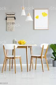 echtes foto einem einfachen natürlichen esszimmer interieur mit len und poster mit gelben blüten über einen runden hölzernen tisch mit