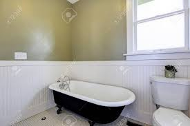 hellgrün und weiß badezimmer mit badewanne auf löwenfüßen und waschbeckenunterschrank