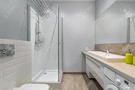 modernes badezimmer mit dusche arbeitsplatte waschmaschine und großem spiegel