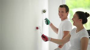 Young Husband And Wife Are Painting The Wall