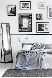 spiegel neben bett mit grauen laken in weiß minimal schlafzimmer int foto bialasiewicz auf envato elements