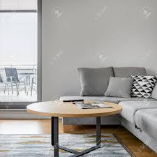 graues sofa mit stilvollem kissen im luxus wohnzimmer mit großem fenster und terrasse