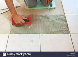 spreading tile adhesive with a notched trowel during process