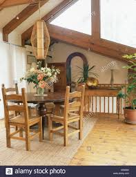 Cylindrical Light Above Circular Mahogany Dining Table And Rush Seated Chairs In Upstairs Room With Rug On Wooden Floor