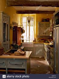 Pale Gray Cupboards In Yellow French Country Kitchen With Terracotta Tiled Floor And Belfast Sink
