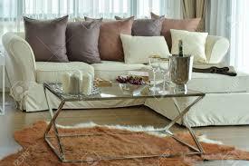 duftkerzen und weingläser auf dem tisch mit beige sofa und dunkelbraunen kissen im modernen wohnzimmer