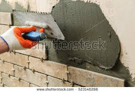 installing tiles on wall worker setting stock photo 523140286