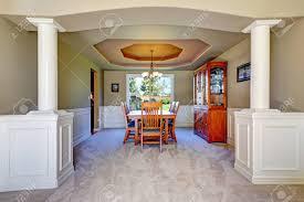 luxus esszimmer mit weißen säulen und oliven wänden kassettendecke und teppichboden