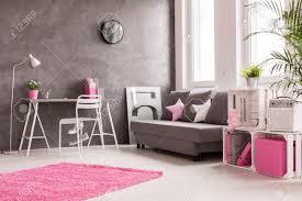 geräumiger innenraum in grau rosa und weiß mit schreibtisch büro le sofa und bücherregal