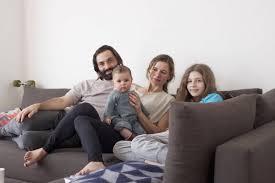 porträt einer familie mit zwei kindern auf dem sofa im