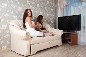entspannte frauen liegen auf dem sofa im wohnzimmer genießen suchen tv