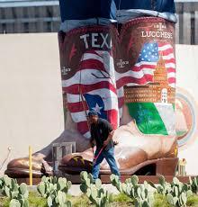 A Worker Walks Near The Boots Of Big Tex 55 Foot Tall