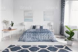 elegante schlafzimmer innenraum mit großen bequemen bett mit bettwäsche gemälde an den wänden und gemusterten teppich auf dem boden echtes foto blau